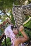 Girl kissing wooden horse head  Stock Photos