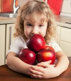 Girl at kitchen with apple Stock Photography