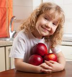 Girl at kitchen with apple Stock Image