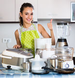 Girl with kitchen appliances at home Stock Photography