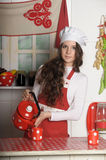 Girl in the kitchen. With an apron and a cup of tea Stock Photos