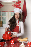 Girl in the kitchen. With an apron and a cup of tea Royalty Free Stock Photography