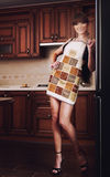 Girl in the kitchen. Beautiful girl with brown hair and long beautiful legs in apron and underwear in the kitchen Royalty Free Stock Photo