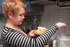 Girl on kitchen with blender Stock Images