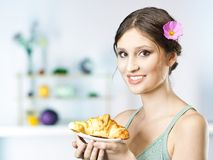 Girl in kitchen with croissant Royalty Free Stock Images