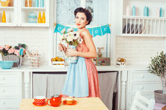 The girl in the kitchen with flowers. Royalty Free Stock Photo