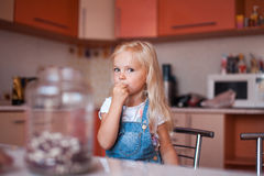 Girl on kitchen with a hand near mouth. Little girl plays on kitchen stock image
