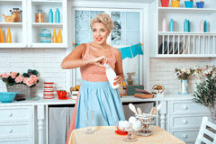 Girl is in the kitchen and holding bottle of milk. Royalty Free Stock Image