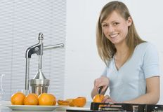 Girl in the kitchen with juicy orange Royalty Free Stock Photo
