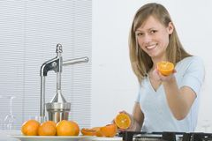 Girl in the kitchen with juicy orange Stock Photos
