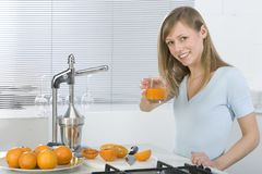 Girl in the kitchen with juicy orange Royalty Free Stock Images