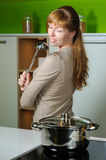 Girl on kitchen with a ladle Royalty Free Stock Image