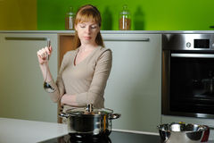 Girl on kitchen with a ladle Stock Images