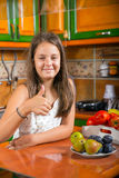 The girl in the kitchen showing thumbs up Stock Image
