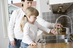 Girl in the kitchen. Small Girl in the kitchen with her mother drinking water Stock Photography
