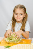 Girl at kitchen table with a slight smile mixes hands in a bowl the grated cheese with herbs Stock Image