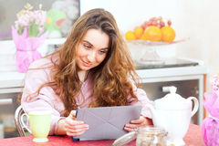 The girl on kitchen with tablet PC Stock Image