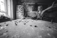Girl on kitchen throws flower. The picture is black and white,there is also a colour version in portfolio stock images