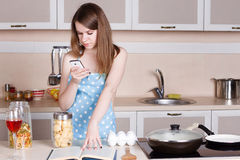 Girl in the kitchen wearing an apron over his naked body prepares and looks into phone Stock Photos