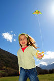Girl and kite. Girl running with a green kite against blue sky Stock Photo
