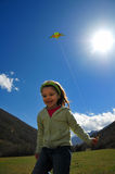 Girl and kite. Girl holding a green kite against blue sky Royalty Free Stock Image