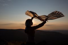 Girl with a kite in their hands. Mountain beautiful sunset. The lights of a sun. Blue-orange sky. Girl with a kite in their hands. Mountain beautiful sunset. The stock photo
