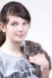 Girl with kitten. Blue-eyed girl holding a cute black kitten Royalty Free Stock Photo