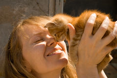 The girl and kitten. The girl holds on hands of a red kitten stock images