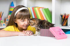 Girl with kitten. Happy little girl opening her gift box and finding a kitten stock photography
