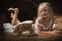Girl with a kitten on hay Royalty Free Stock Photography