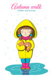 Girl and kitten in the rain. Autumn walk. Children and animals. Girl holding a kitten and standing in a puddle in the rain Stock Photo