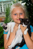 Girl with kittens. The girl is holding two small colored kittens stock photo