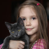 Girl and kitty. Sweet portrait of a cute little girl holding and snuggling a gray kitten Royalty Free Stock Photos