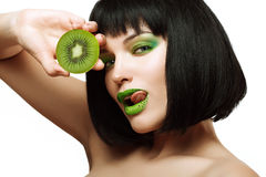 Girl with kiwi. Bright makeup. Sexy girl with a delicious kiwi. Bright green makeup Royalty Free Stock Photos