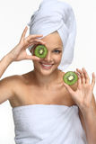 Girl with kiwi mask. Beautiful blonde girl in towel with kiwi - on white Royalty Free Stock Photography