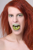 Girl with kiwi slice on her mouth Stock Photography