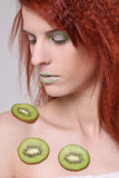 Girl with kiwi slices on her skin Royalty Free Stock Image