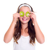 Girl with kiwi slices over her eyes Stock Photography