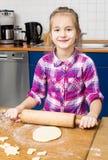 Girl kneading dough with rolling pin. Stock Photos