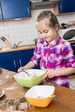 Girl kneading dough with rolling pin on table Royalty Free Stock Image