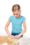 Girl kneads dough for pie on kitchen table isolated Royalty Free Stock Photography