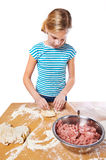 Girl kneads dough for pie on kitchen table isolated Royalty Free Stock Photos