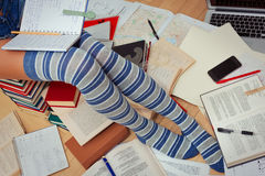 Girl in knee-height socks is studying sitting on the books. Teen in knee-height striped socks is preparing for school, college or university exams stock photos