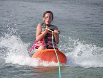 Girl Kneeboarding. A teenage girl kneeboarding in a lake Stock Image