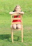 Girl kneeing on chair Stock Images