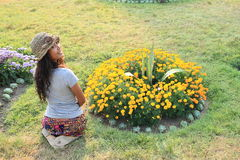 Girl kneeing in front of flowers Royalty Free Stock Photo
