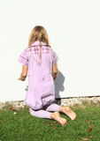 Girl kneeing in front white wall Royalty Free Stock Images