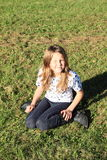 Girl kneeing on grass Royalty Free Stock Image