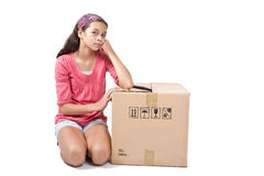 Girl kneeling by an empty cardboard box. Royalty Free Stock Images