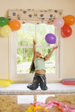 Girl (4-6) kneeling on window seat at home, catching falling party balloon, arms up, smiling, front view Royalty Free Stock Image
